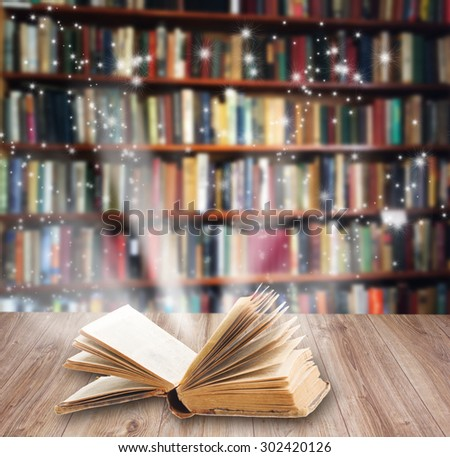 Open book on wooden book shelf with magic light  #302420126