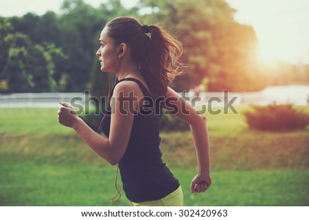 Pretty sporty woman jogging at park in sunrise light Royalty-Free Stock Photo #302420963