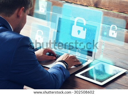 Business, technology, internet and networking concept. Young businessman working on his laptop in the office, select the icon  security on the virtual display. Royalty-Free Stock Photo #302508602