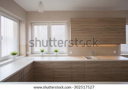 Simple modern spacious kitchen with wooden furniture #302517527