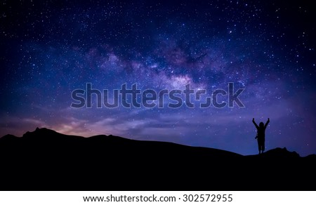 Silhouette of a happy photographer adventure trekking on  mountain with real fantasy stars and milky way in the night sky. Conceptual of amazing nature with great dream journey and voyage scene.