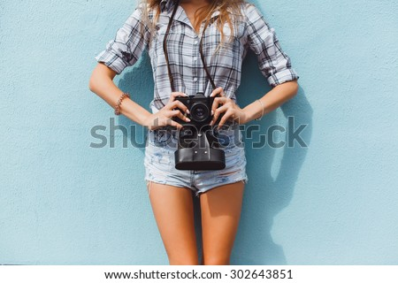 young beautiful brunette girl with a beautiful face and figure, hipster, retro posing with a camera on the outside, making photos, taking pictures, woman, photographer,vintage camera, outdoor portrait