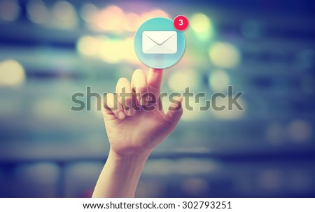 Hand pressing an email icon on blurred cityscape background  #302793251