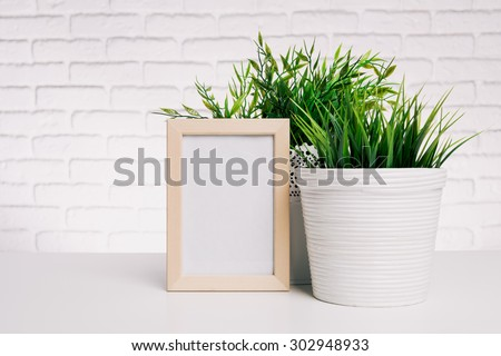 Blank small wooden photo frame and house plants #302948933