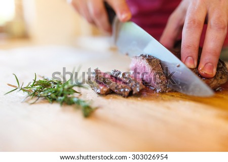 Man slicing a grilled beef stead on a wooden cutting board #303026954