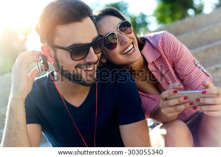 Portrait of two friends using mobile phone and listening to music in the street. #303055340