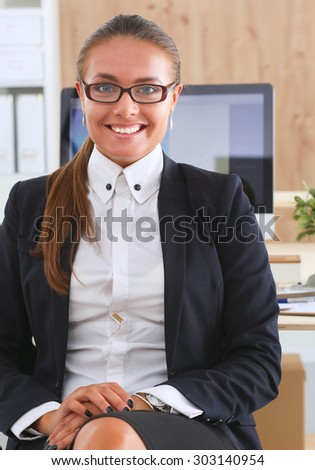 Young woman working in office, sitting at desk #303140954