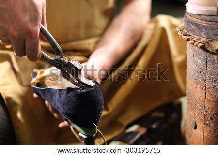 Making shoes. Shoemaker performs shoes in the studio craft Royalty-Free Stock Photo #303195755
