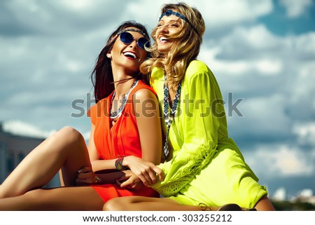 Fashion portrait of young hippie women girls in summer sunny day in bright colorful cloth #303255212