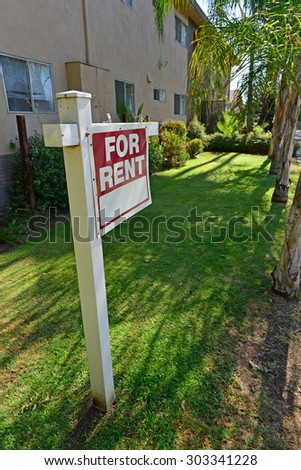 "A sign proclaiming ""FOR RENT"" stands in front of an apartment building. #303341228"