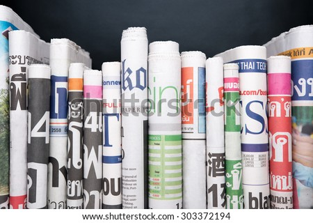 Newspapers folded and stacked Royalty-Free Stock Photo #303372194