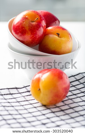 sweet, organic red and yellow plums in a white bowl, isolated on white background by the window with checkered table cloth, close up, vertical #303520040