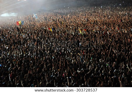 CLUJ NAPOCA, ROMANIA - AUGUST 1, 2015: Crowd of cheerful young people having fun during an Armin van Buuren concert at Untold Festival  #303728537