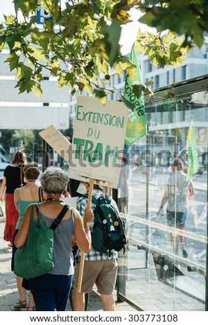 STRASBOURG, FRANCE - AUG 6, 2015: People wearing air masks protesting against air pollution in Strasbourg, Alsace, France - people walking near bus station with placard: please  extend the tramway #303773108
