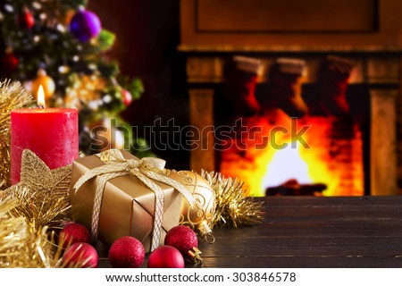 Christmas decorations, a gift and a candle in front of a fireplace. A fire is burning in the fireplace and Christmas stockings are hanging on the mantelpiece. #303846578