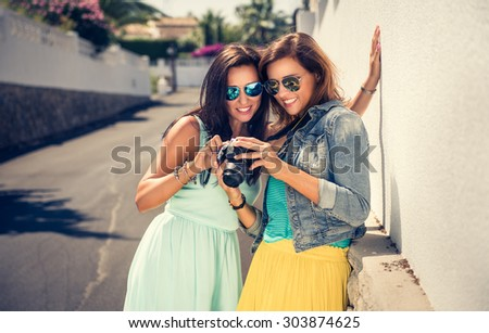Outdoor lifestyle fashion portraits of two sisters in modern, colorful clothes, with digital camera. Two friends hugs and posing at the street, having fun. Women looking at the camera.