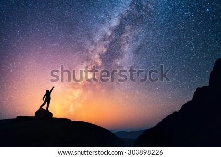 Star-catcher. A person is standing next to the Milky Way galaxy pointing on a bright star. Royalty-Free Stock Photo #303898226