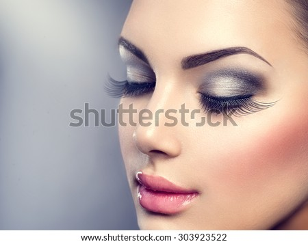 Beautiful Fashion Luxury Makeup, long eyelashes, perfect skin facial make-up. Beauty Brunette model woman holiday make up close up. Eyelash extensions, false eyelashes.  Royalty-Free Stock Photo #303923522