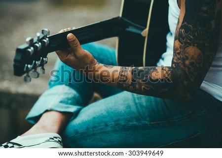 Man with tattoos playing guitar #303949649
