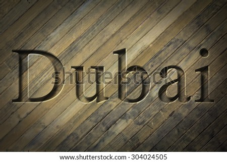 Engraving spelling the city Dubai on textured old surface #304024505