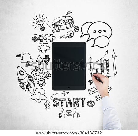 A tablet, digital device is surrounded by drawn business icons. A hand is drawing a bar chart. Concrete background.