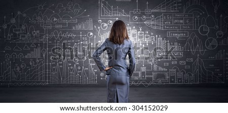 Rear view of businesswoman looking at chalk business sketches on wall #304152029