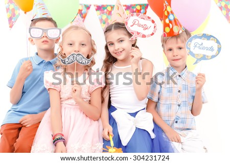 Creative picture. Portrait of little cute children holding small tags with birthday related signs during party
