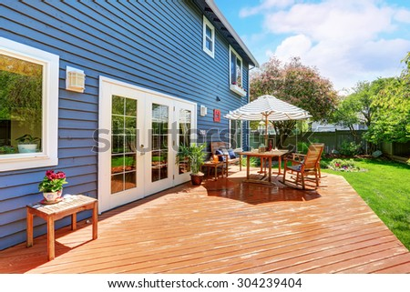 Picture perfect back deck with umbrella covered seats and lots of grass.