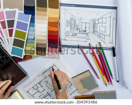 Top view of architects hands drawing of modern house with material sample on creative desk Royalty-Free Stock Photo #304391486