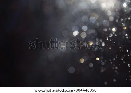 Abstract elegant glitter sparkle bokeh defocused on black background