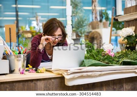Shocked mid adult female florist holding glasses while using laptop at counter in flower shop #304514483