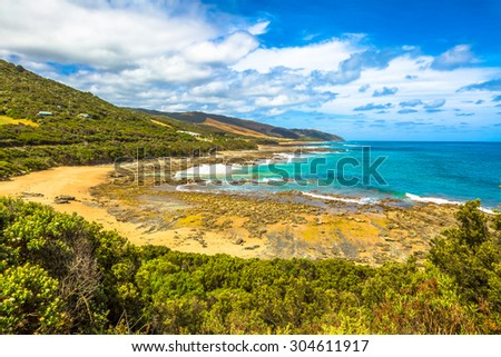 Spectacular view of the Great Ocean Road with its famous mountains, the winding road, cliffs, rocky beaches, the turquoise sea and its waves for surfing. #304611917