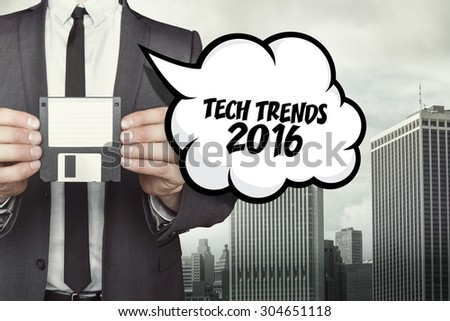 Tech trends 2016 text on speech bubble with businessman holding diskette on cityscape background