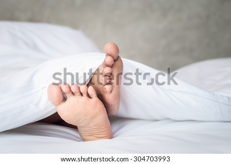 Close up feet of women on white bedding in the morning time #304703993