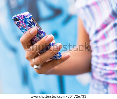 Female Hands holding smartphone. Young tanned  woman holding mobile phone,checking news and typing sms, wearing blue dress and ring.Mobile in bright cover. Royalty-Free Stock Photo #304726733