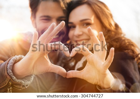 Closeup of couple making heart shape with hands #304744727