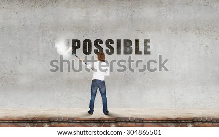 Man changing word impossible in to possible by erasing part of word with paint roller #304865501