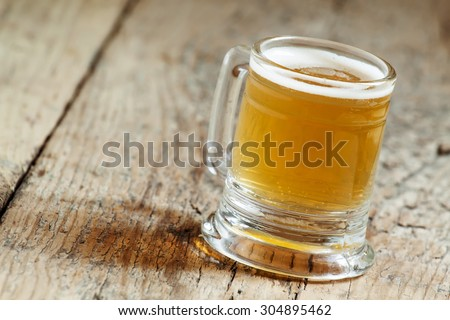 light beer in a little old-fashioned mug on old wooden table, selective focus #304895462