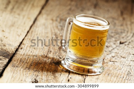 light beer in a little old-fashioned mug on old wooden table, selective focus #304899899