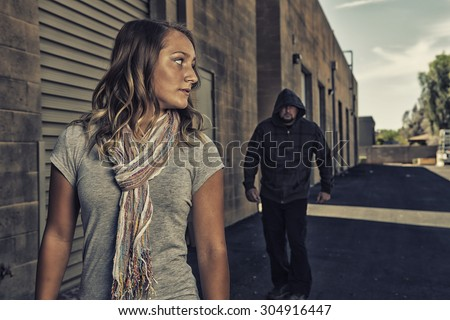 GIRL SELF DEFENSE | A young woman sees a suspicious person walking behind her and plans to defend herself against a male attacker in an alley. Refuse to be a victim.    Royalty-Free Stock Photo #304916447
