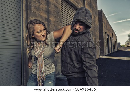 GIRL SELF DEFENSE | A young woman defends herself against a male attacker in an alley by elbowing him in the jaw. Refuse to be a victim.    Royalty-Free Stock Photo #304916456