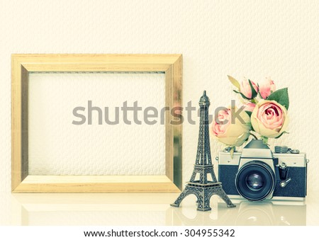 Golden picture frame, rose flowers and no name vintage camera. Nostalgic decoration with space for your photo or text. Paris travel concept. Retro style toned picture