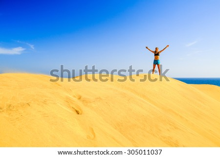Young woman success business concept on beautiful inspirational beach dunes on sunny summer day. Beauty female runner jogging and exercising, success motivation and inspiration outdoors in nature Royalty-Free Stock Photo #305011037