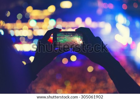 Man holding phone and recording a concert, taking pictures and enjoying the music festival party