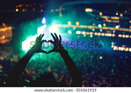 Heart shaped hands at concert, loving the artist and the festival. Music concert with lights and silhouette of a man enjoying the concert Royalty-Free Stock Photo #305061929