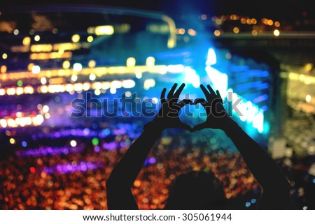 Silhouette of a man making heart from hand gestures, vintage look on photo and crowd background Royalty-Free Stock Photo #305061944