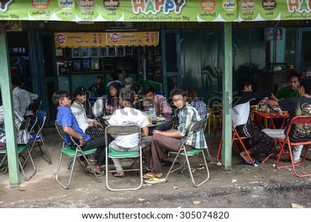 SAGAING HILL, MYANMAR - JULY 31, 2015: people at restaurant around temple at the top of Sagaing hill near Mandalay, great tourist attraction. #305074820