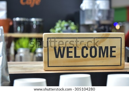 Welcome black letters printed on soft pine putting guests at the shop.