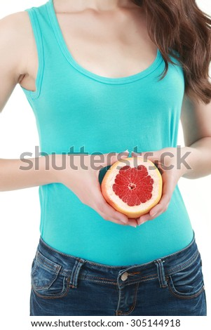 A portrait of a tasty woman holding a juicy grapefruit under her chin. #305144918