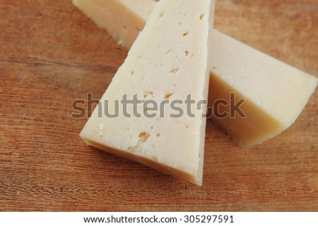 two fresh triangle french delicacy parmesan cheese pieces on wooden cut board over table #305297591
